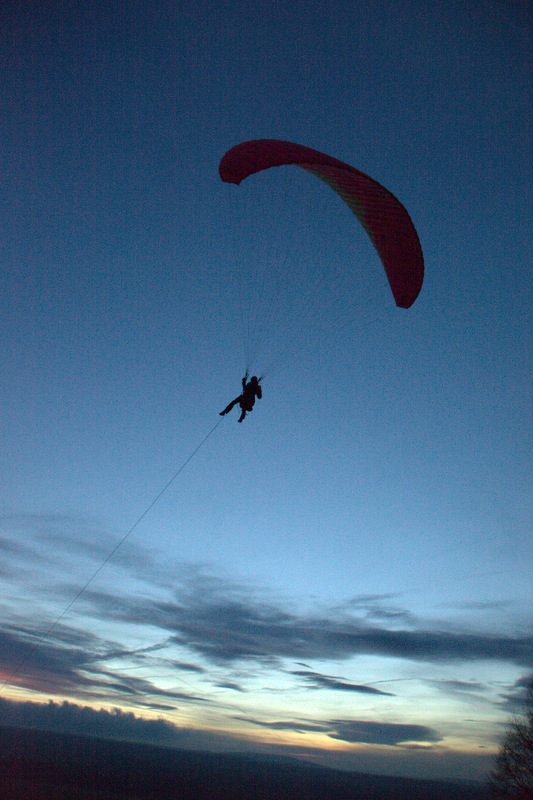 Mit einem Seil wird der Gleitschirm samt Pilot gegen den Wind nach oben gezogen